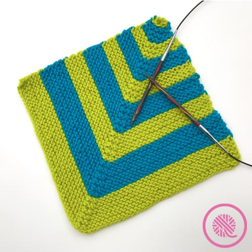 green and blue mitered square with knitting needles